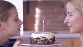 Mamã do feliz aniversario, mãe nova com velas de sopro da menina da criança no bolo do feriado e sorrisos e para olhar se