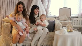 Mamã dois com o rapaz pequeno e a menina que sentam-se em uma sala de estar no estúdio do Natal video estoque