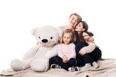 A mamã, duas filhas e um urso de peluche estão sentando-se e estão abraçando-se, fechando seus olhos Fotos de Stock Royalty Free