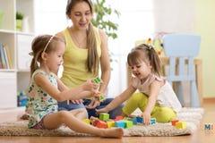 A mamã e as filhas da família que jogam com bloco brincam na sala de visitas fotografia de stock