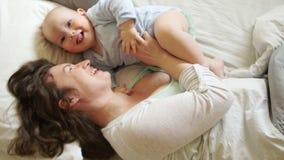 Mamã e bebê ensolarados da manhã da família na cama Uma mulher agrada e abraça seu filho de um ano Dia de matrizes video estoque
