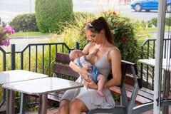 Mamã e bebê novos fora durante o dia de verão bonito, mulher no vestido cinzento que senta-se no terraço com vista da rua foto de stock