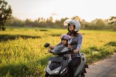 A mamã e a criança apreciam montar o 'trotinette' da motocicleta imagens de stock royalty free