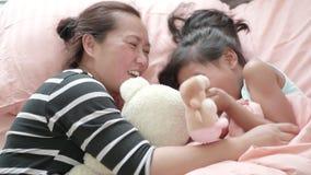 A mamã e a criança bonita estão jogando na sala de visitas vídeos de arquivo