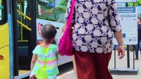 Mamã e criança em uma parada do ônibus, esperando o ônibus video estoque