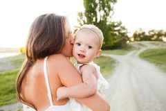 Mamã e a criança A criança está sentando-se com sua mãe em seus braços ao andar na natureza foto de stock