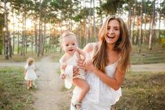 Mamã e a criança A criança está sentando-se com sua mãe em seus braços ao andar na natureza imagem de stock