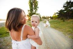 Mamã e a criança A criança está sentando-se com sua mãe em seus braços ao andar na natureza fotos de stock