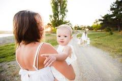 Mamã e a criança A criança está sentando-se com sua mãe em seus braços ao andar na natureza imagens de stock royalty free