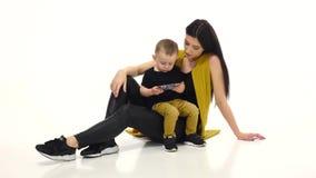 A mamã e a criança estão olhando desenhos animados em um smartphone Fundo branco vídeos de arquivo