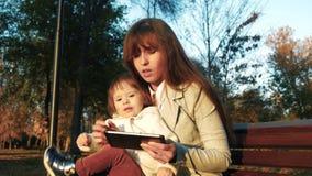 A mamã e a criança estão sentando-se no banco no livro de leitura do parque na tabuleta video estoque