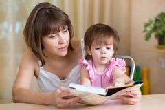 A mamã e a criança leram um livro Fotografia de Stock Royalty Free