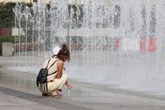 A mamã e a criança perto do refrescamento espirram da fonte da cidade do verão Banho e resto em seu tempo livre nos raios do imagem de stock