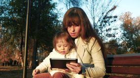 A mamã e a criança sentam-se no parque em um banco e jogam-se na tabuleta video estoque
