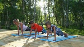 A mamã e dois meninos que executam a ioga levantam fora vídeos de arquivo