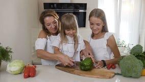 Mamã e dois que suas filhas cozinham na cozinha: a mulher corta vegetais, pimentas verdes para fazer uma salada, e ensina video estoque
