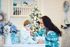 A mamã e a filha abrem um presente em um humor do Natal Foto de Stock Royalty Free
