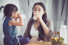 A mamã e a filha asiáticas felizes da família bebem o leite fotos de stock royalty free