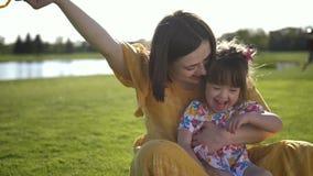 Mamã e filha bonita que riem no prado filme