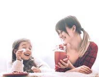 Mamã e filha bonito pequena que comem doces do Natal fotos de stock