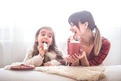 Mamã e filha bonito pequena que comem doces do Natal fotos de stock royalty free