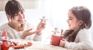 Mamã e filha bonito pequena que comem doces do Natal imagem de stock