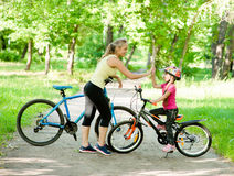 A mamã e a filha dão a elevação cinco ao dar um ciclo no parque Fotos de Stock