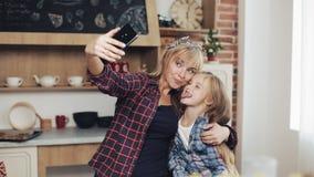Mamã e filha de sorriso que fazem a foto do selfie com câmera do smartphone em casa na cozinha Família, cozinheiro, e conceito do filme