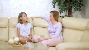 Mamã e filha do conceito de uma comunicação a mãe e a filha têm o assento de conversa do divertimento no sofá na sala de visitas video estoque