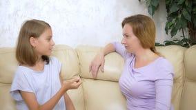 Mamã e filha do conceito de uma comunicação a mãe e a filha têm o assento de conversa do divertimento no sofá na sala de visitas vídeos de arquivo