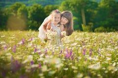 A mamã e a filha em um piquenique na camomila colocam Dois louros bonitos na camomila colocam em um fundo do cavalo Fotografia de Stock Royalty Free