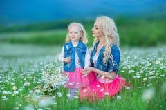 A mamã e a filha em um piquenique na camomila colocam Dois louros bonitos que vestem o revestimento das calças de brim e o gir co Imagem de Stock Royalty Free