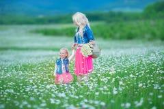 A mamã e a filha em um piquenique na camomila colocam Dois louros bonitos que vestem o revestimento das calças de brim e o gir co Imagens de Stock Royalty Free