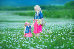 A mamã e a filha em um piquenique na camomila colocam Dois louros bonitos que vestem o revestimento das calças de brim e o gir co Foto de Stock