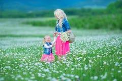 A mamã e a filha em um piquenique na camomila colocam Dois louros bonitos que vestem o revestimento das calças de brim e o gir co Imagem de Stock