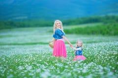 A mamã e a filha em um piquenique na camomila colocam Dois louros bonitos que vestem o revestimento das calças de brim e o gir co Fotos de Stock Royalty Free