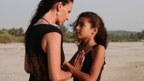 A mamã e a filha estão cara a cara, as mãos hplding e a obtenção mais perto vídeos de arquivo