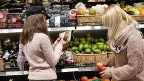 A mamã e a filha estão comprando o fruto vídeos de arquivo