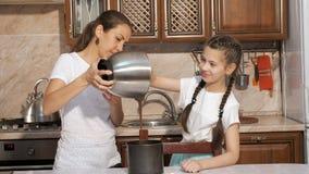 A mamã e a filha estão cozinhando um bolo de esponja junto na cozinha em casa filme