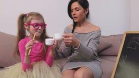 A mamã e a filha estão gracejando, comem e bebem no sofá filme
