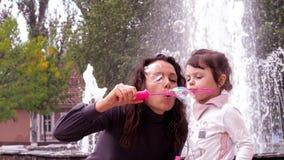 A mamã e a filha estão jogando com bolhas de sabão A mamã com uma criança pequena na fonte infla bolhas de sabão filme