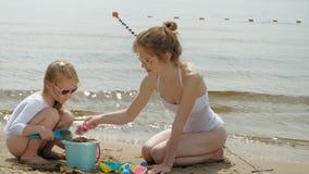 A mamã e a filha estão jogando na praia, construindo um castelo da areia Dia ensolarado do ver?o f?rias filme