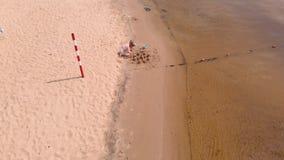 A mamã e a filha estão jogando na praia, construindo um castelo da areia Dia ensolarado do ver?o f?rias Tiro a?reo vídeos de arquivo