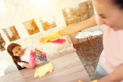 A mamã e a filha estão limpando em casa Estão ao lado da mesa de jantar e enganam ao redor imagem de stock royalty free