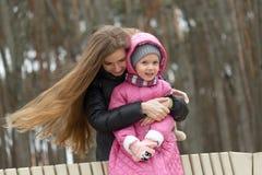 A mamã e a filha estão sentando-se em um banco de parque foto de stock