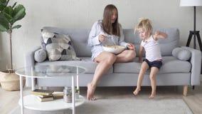A mamã e a filha estão sentando-se no sofá em seu pijama vídeos de arquivo