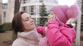 A mamã e a filha estão tendo o divertimento O bebê e a mamã dizem um verso na rua video estoque