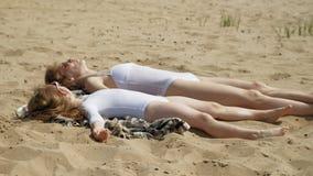 A mamã e a filha estão tomando sol na praia Dia ensolarado do ver?o vídeos de arquivo
