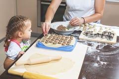 A mamã e a filha fazem junto bolinhas de massa na cozinha Foto de Stock Royalty Free