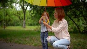 Mamã e filha felizes sob o guarda-chuva colorido video estoque